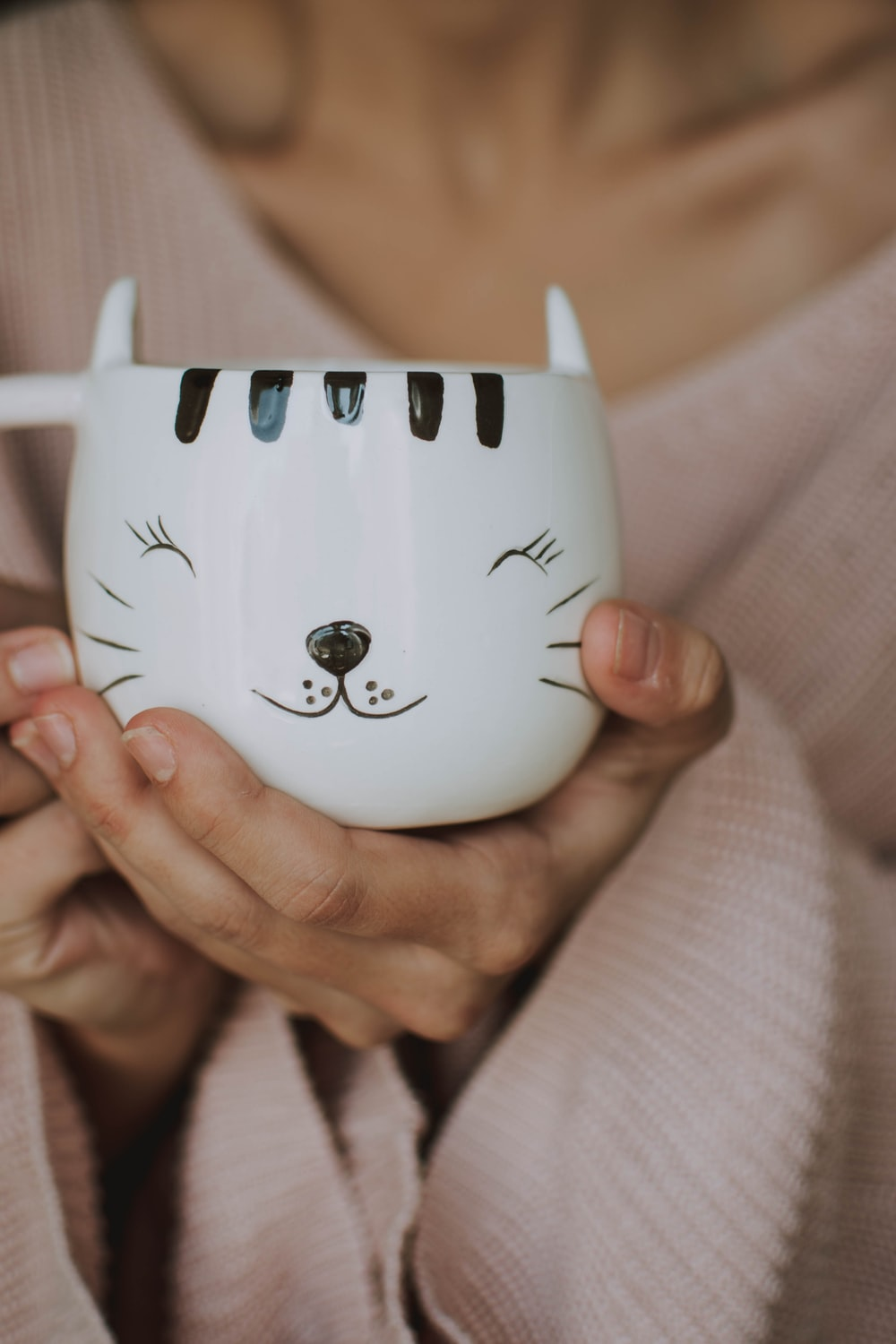 person holding white and black cat graphic teacup