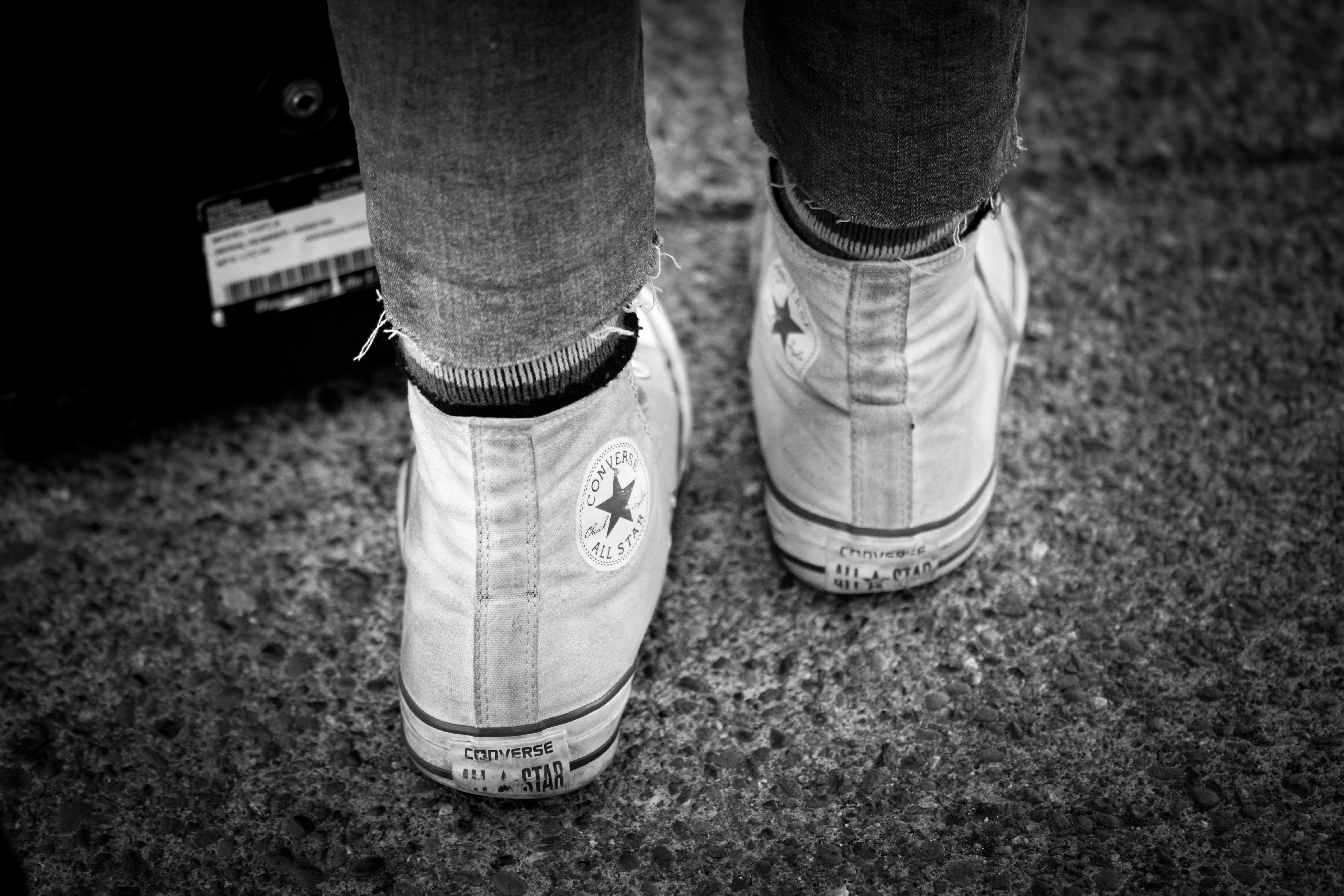 grayscale photography of person wearing Converse All-Star high-top sneakers