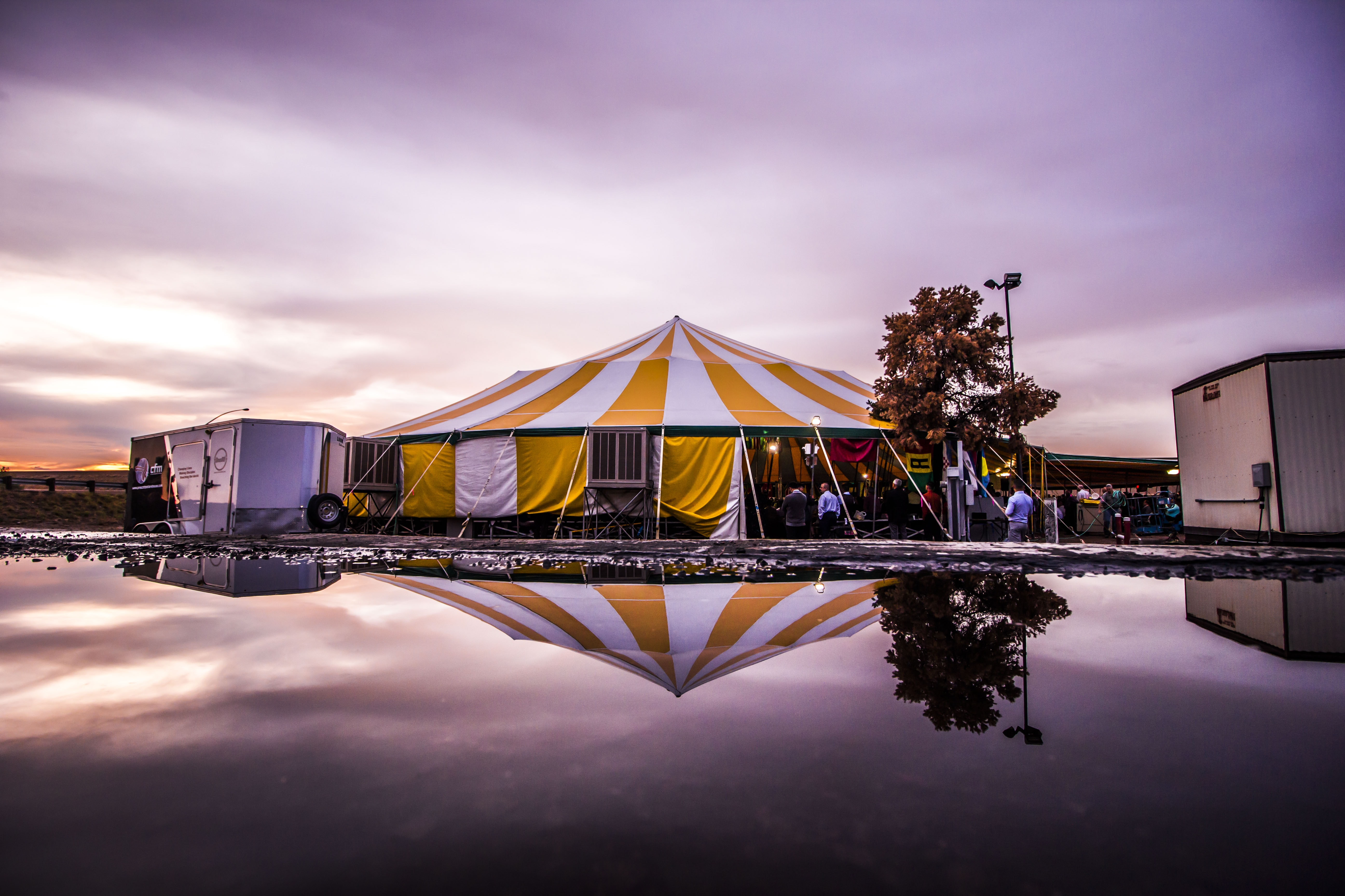 white and yellow striped carnival tent near body of water