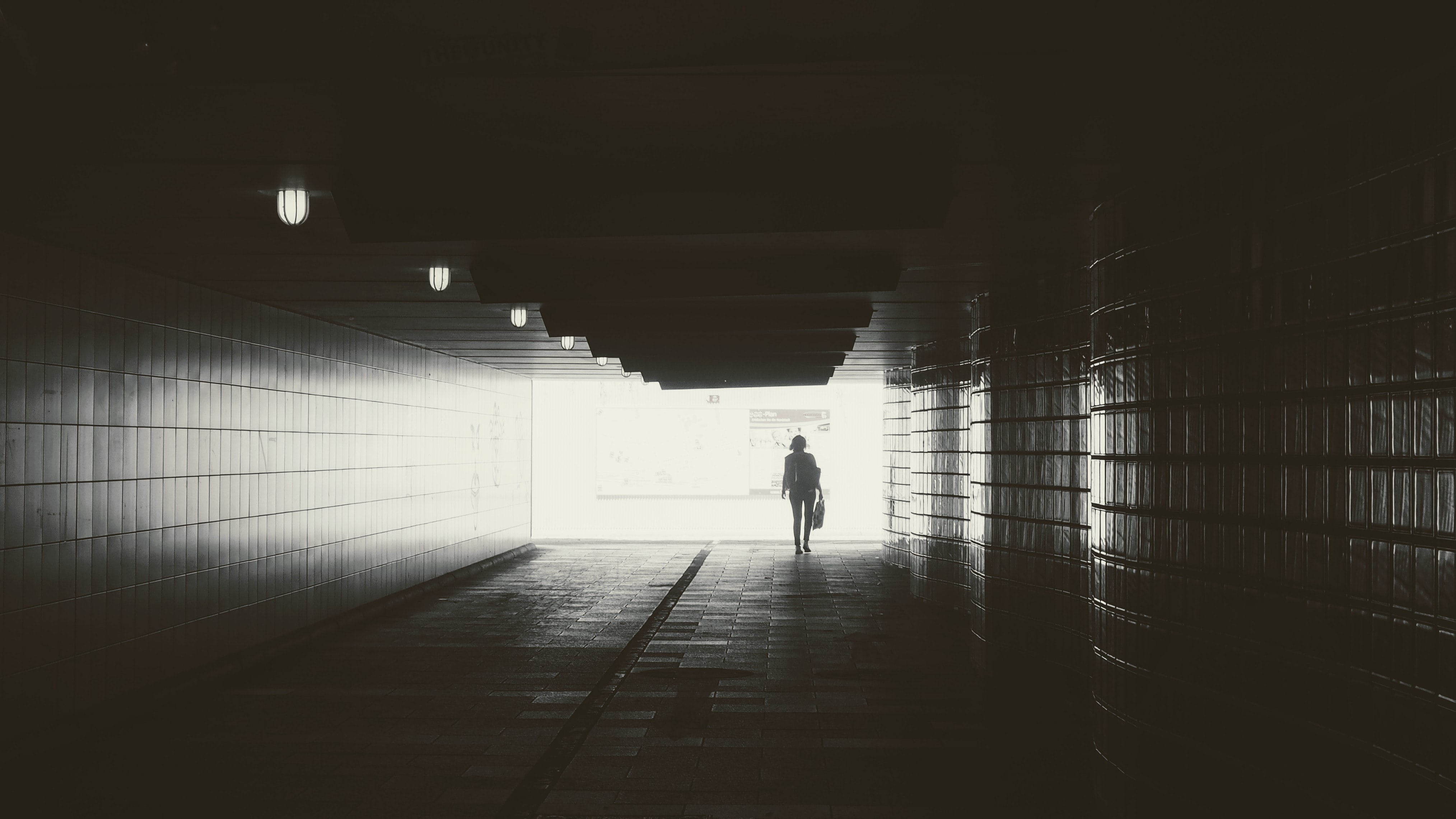 gray scale photography of person walking in bridge