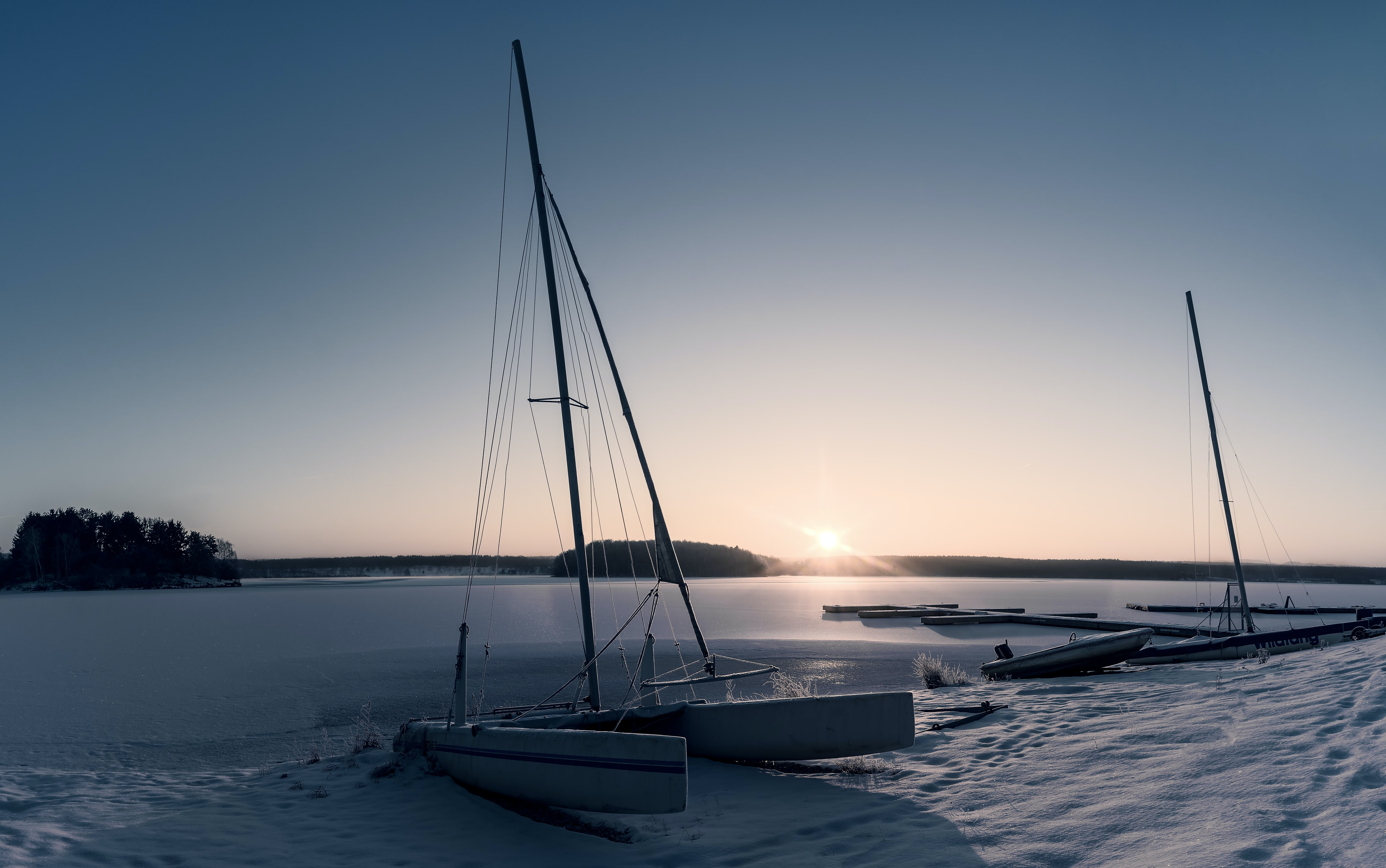 white boat on the seashore during golden hour