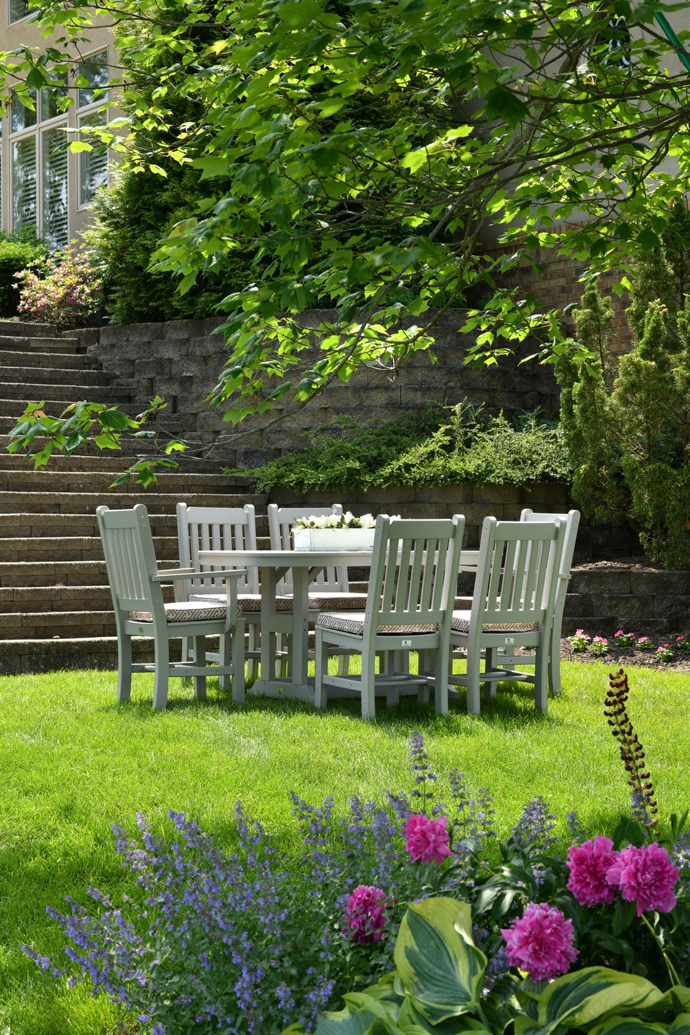 white wooden dining table with chairs set on grass