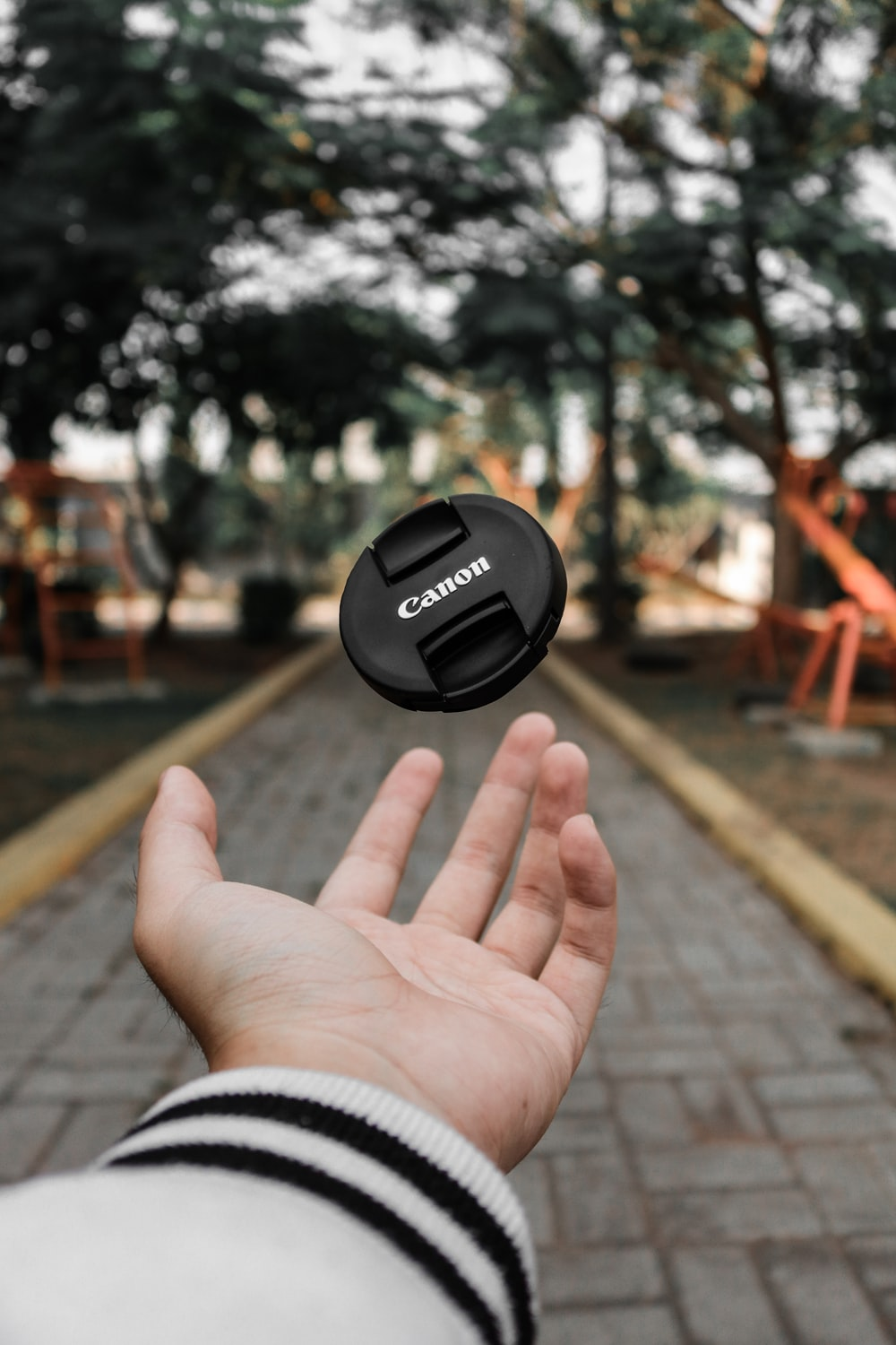 selective focus photo of person's hand throw the cover of DSLR camera