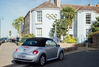 gray Volkswagen New Beetle coupe parked near white concrete house