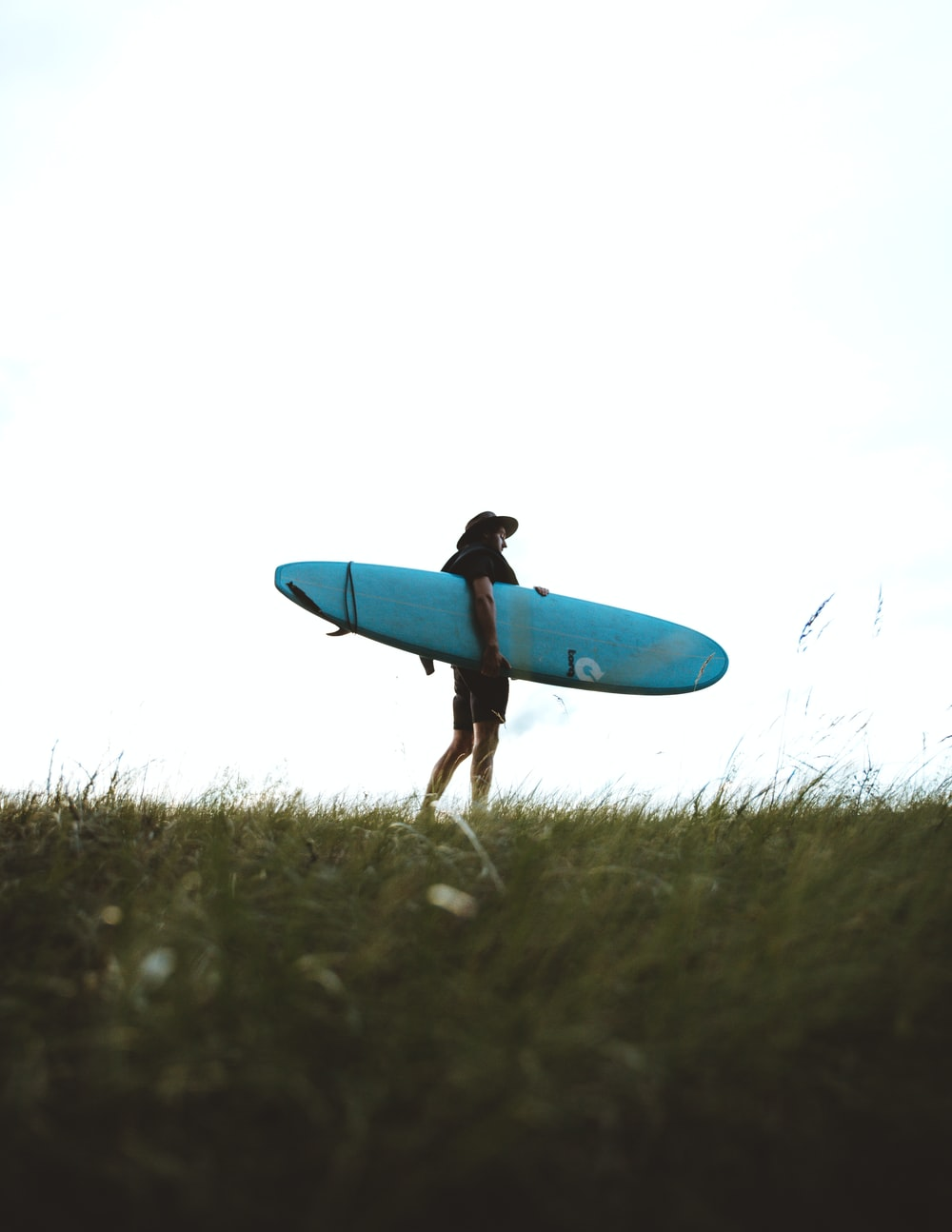 man holding teal surfboard at daytime