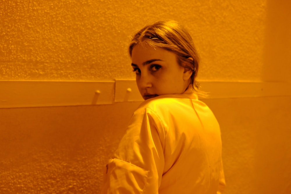 woman wearing white top near wall
