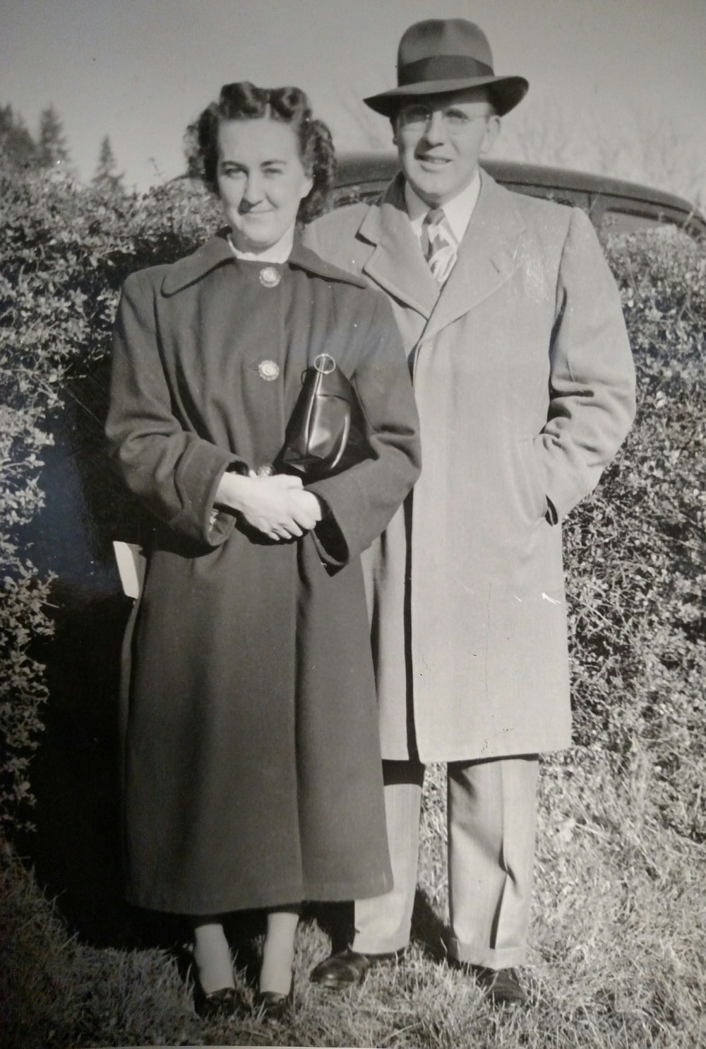 grayscale photography of man and woman wearing coat