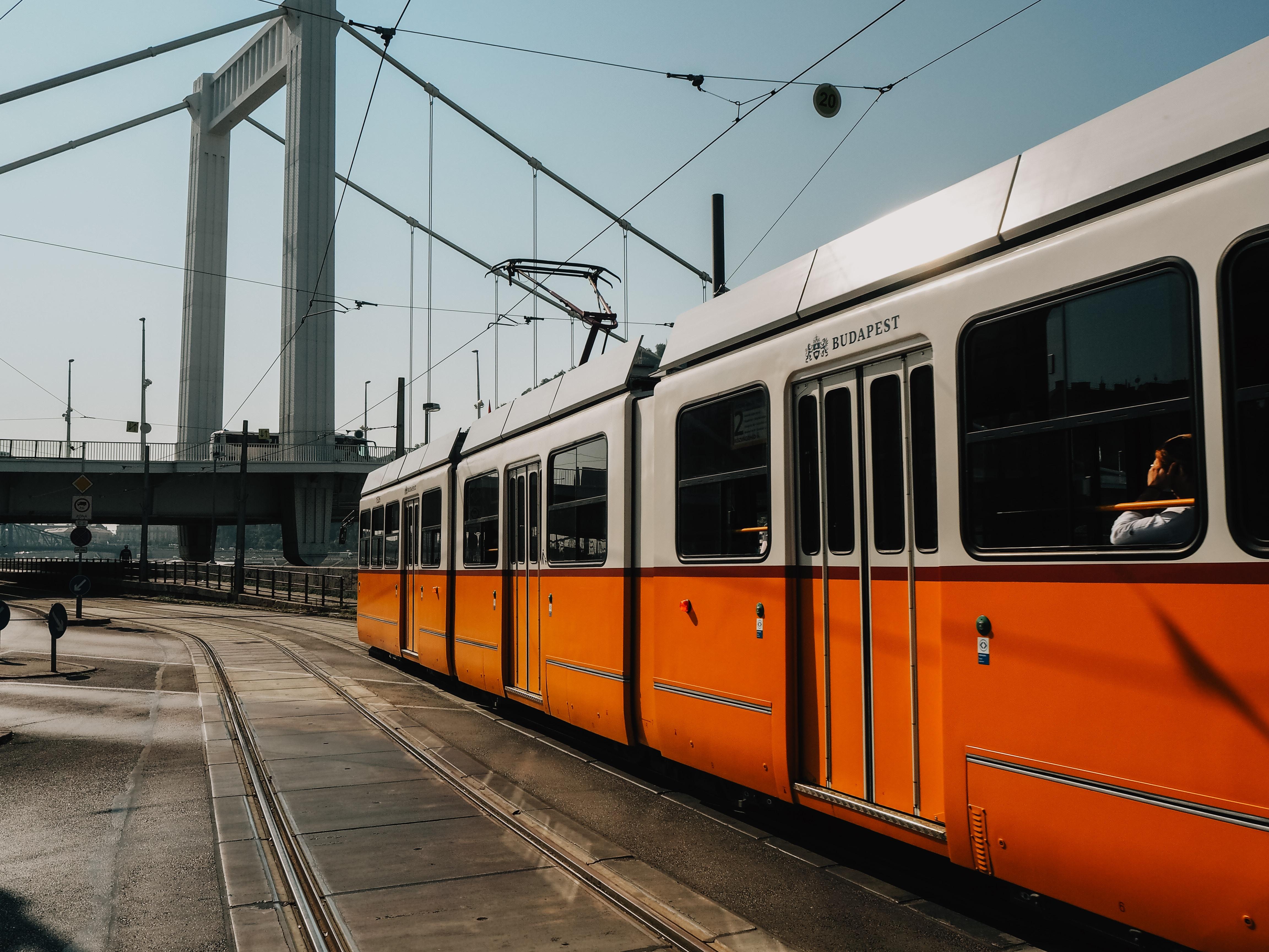 white and orange train near suspension bridge