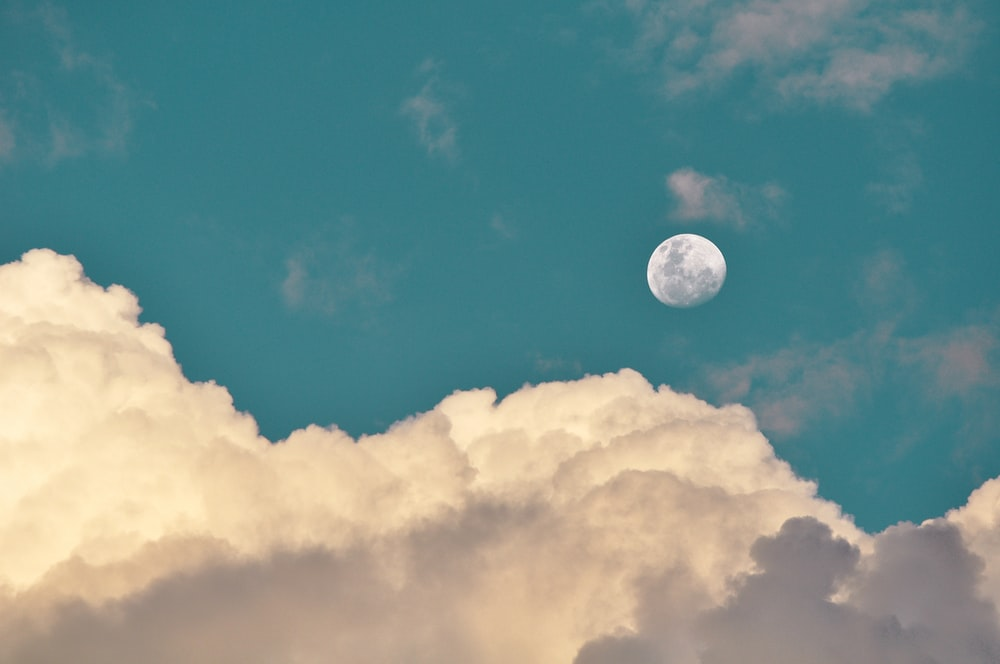 low-angle photography of moon and clouds