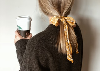 woman in black sweater holding starbucks coffee cup