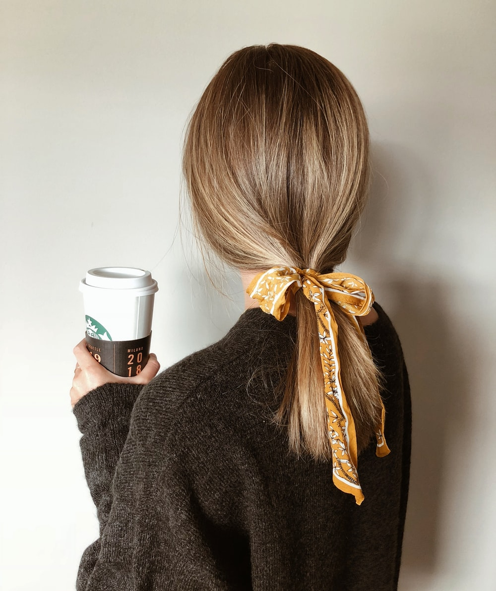 woman in black sweater holding starbucks coffee cup