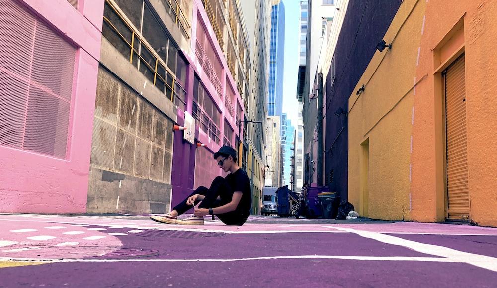 man sitting on ground near building