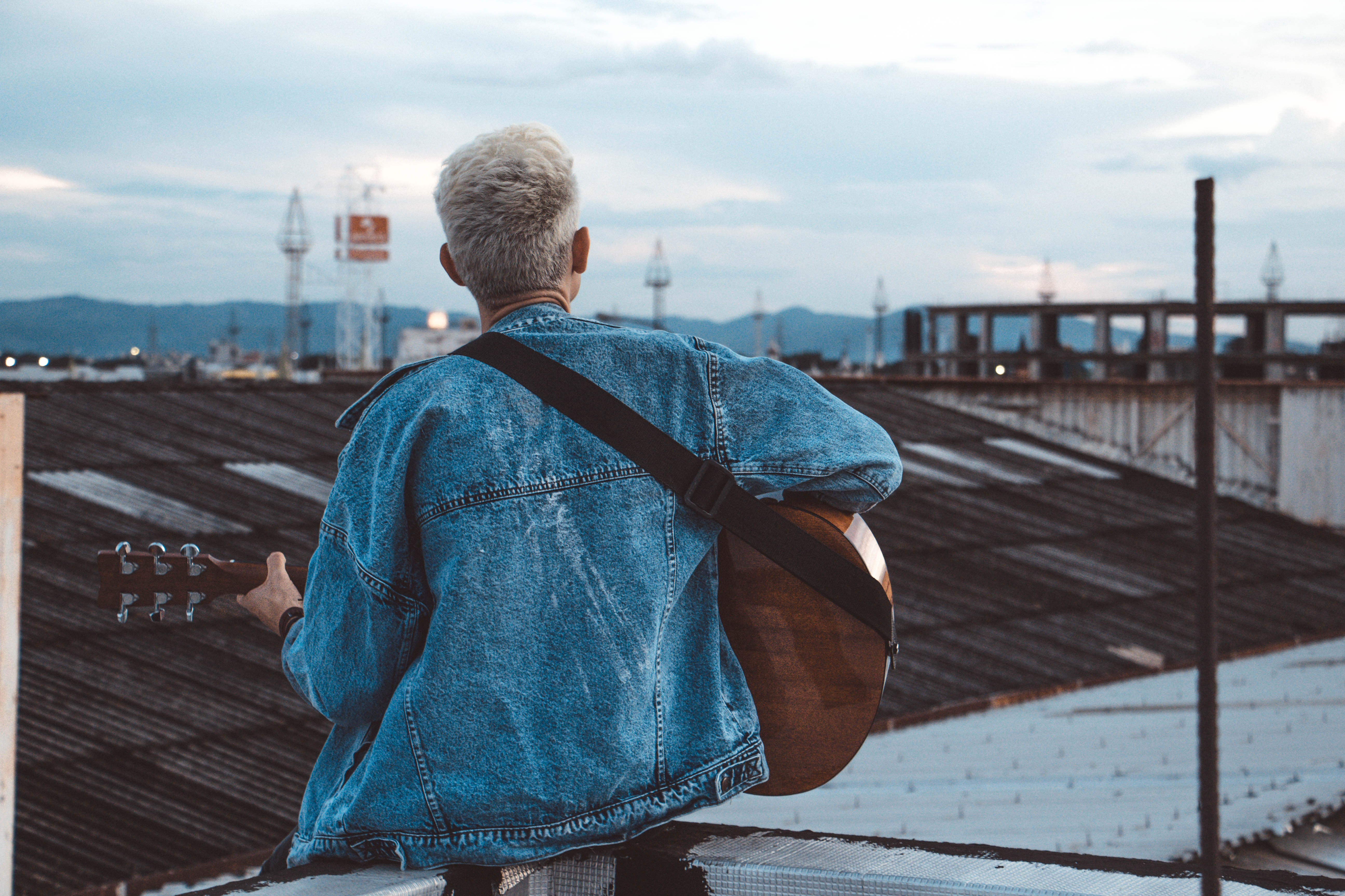 person playing guitar on rooftop