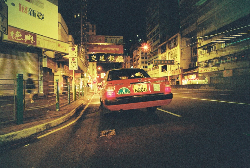 red vehicle on road during nighttime