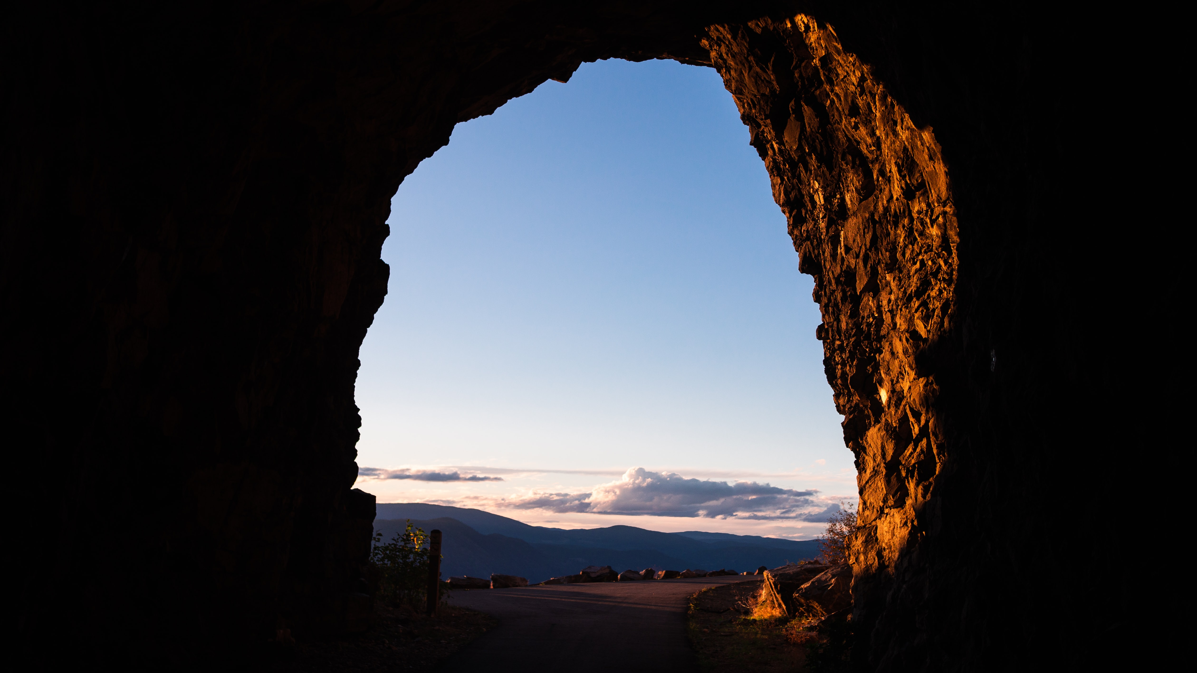 cave entrance with clouds and mountain in background