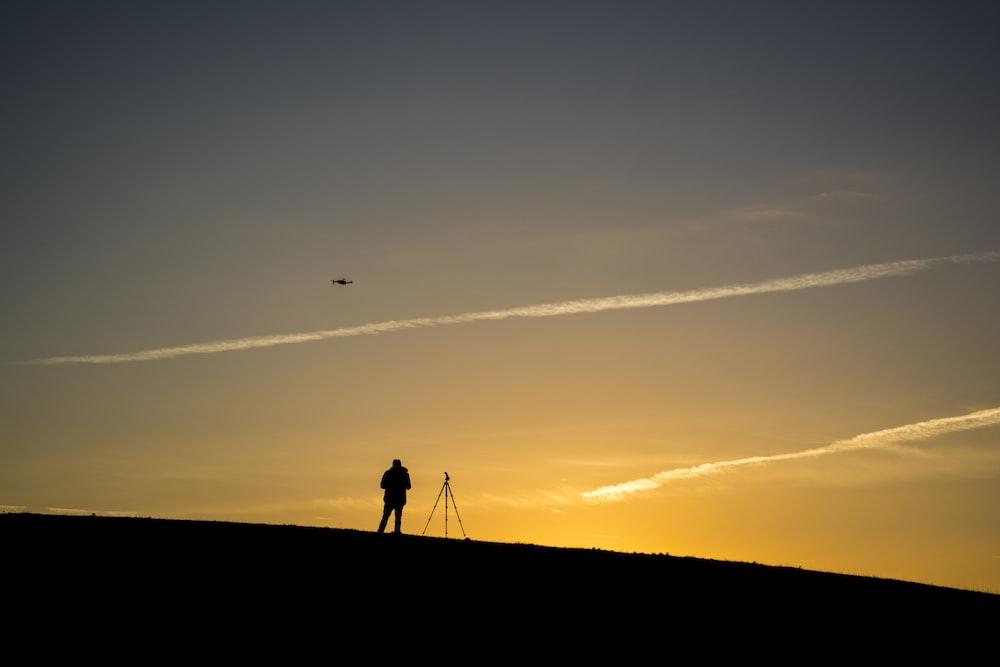 silhouette of person beside tripod