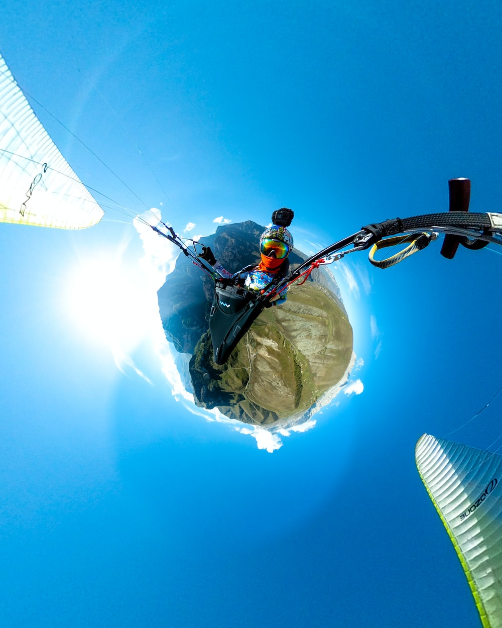 man standing on top of tower pole in little planet photography