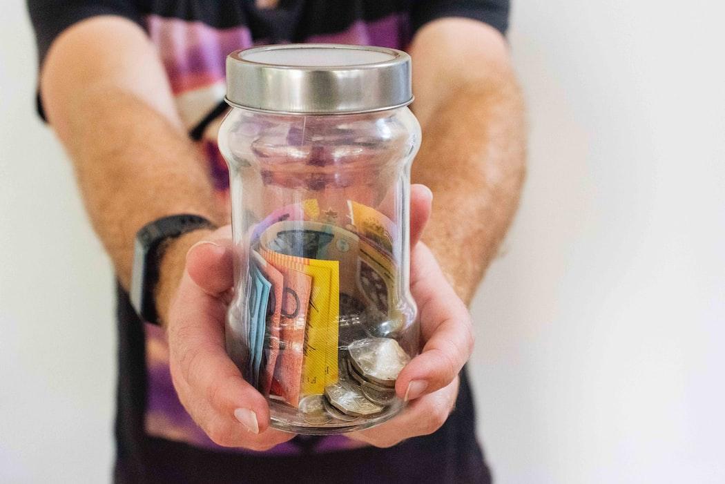 Na foto um homem segura um pote com dinheiro. | Texto - Confira 11 dicas que vão te ajudar a como organizar sua vida financeira e fazer o dinheiro trabalhar para você.