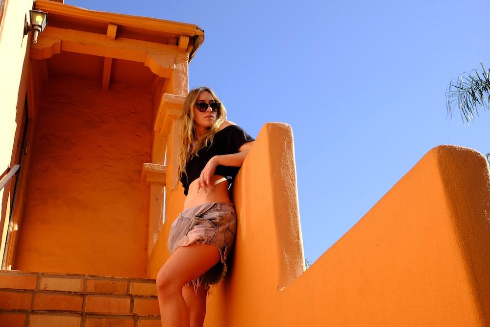 woman leaning beside orange wall