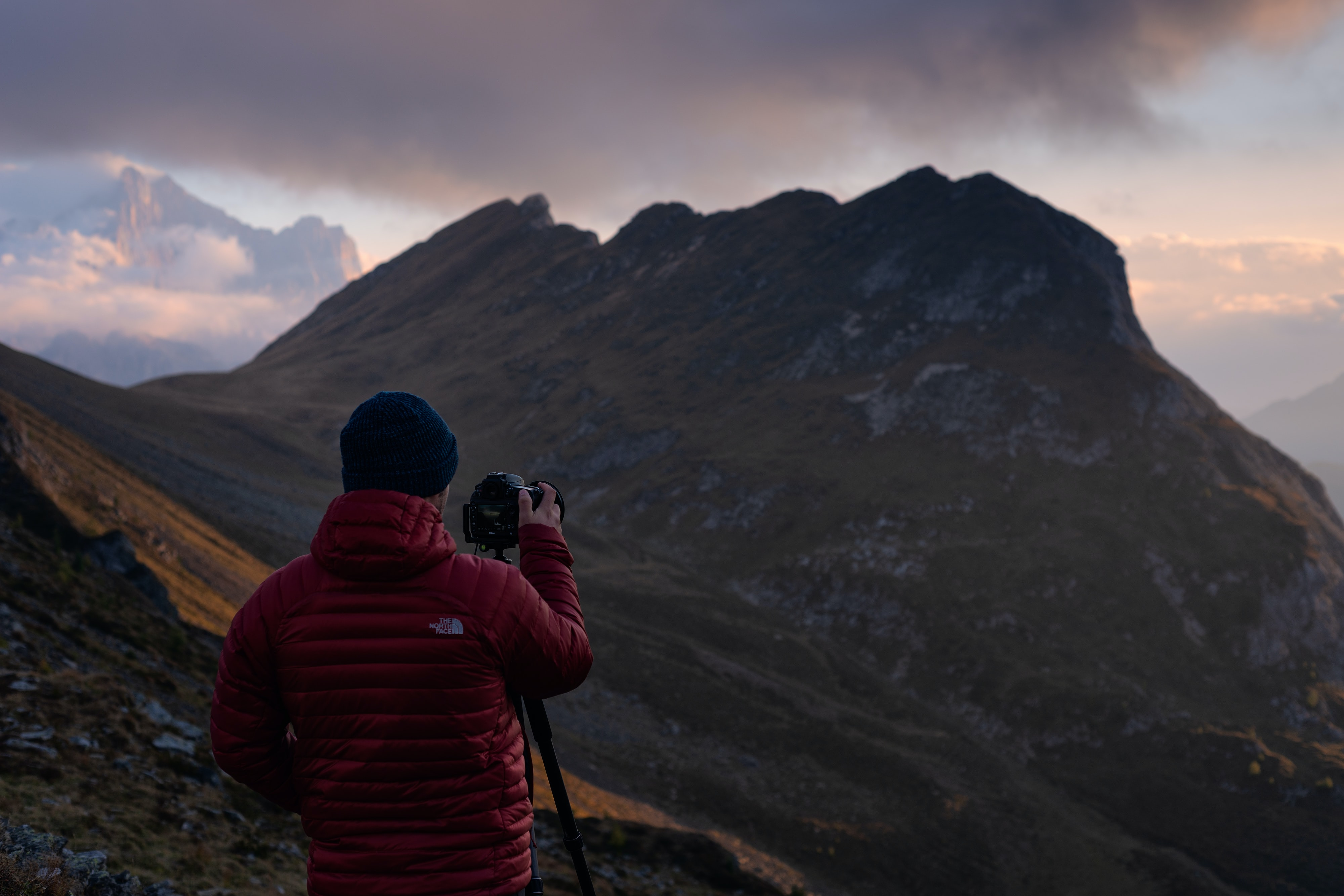 man aiming camera on mountain range
