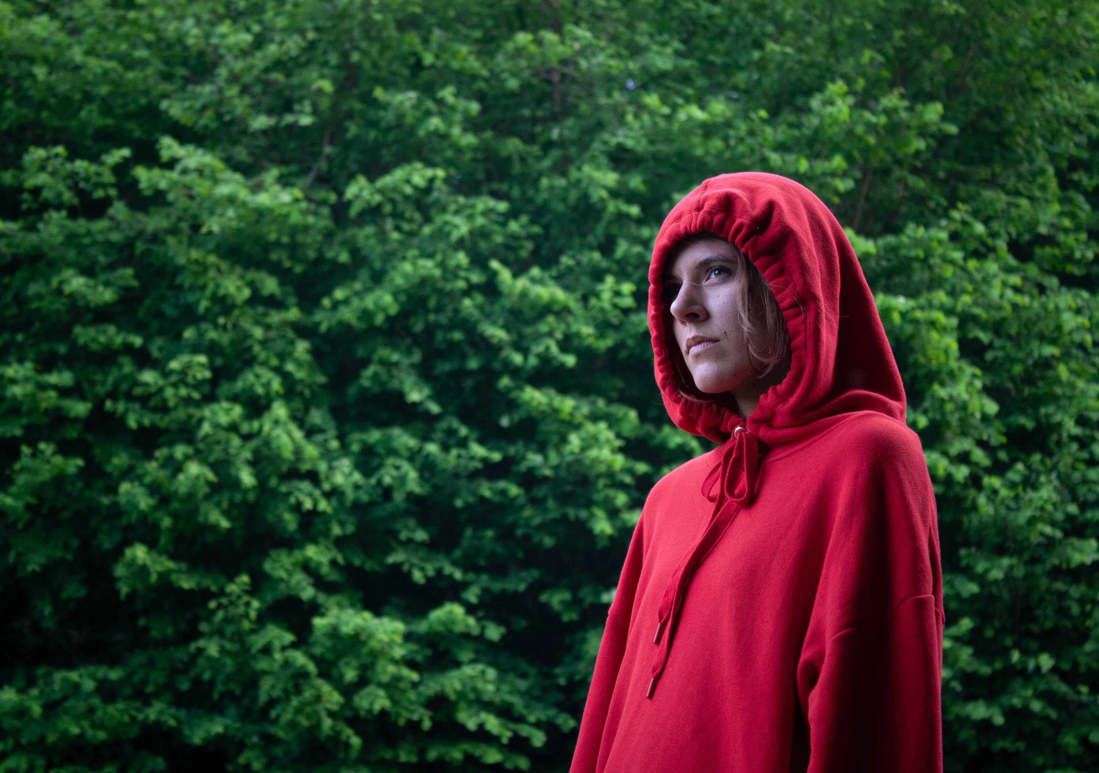 standing woman in red hoodie near trees