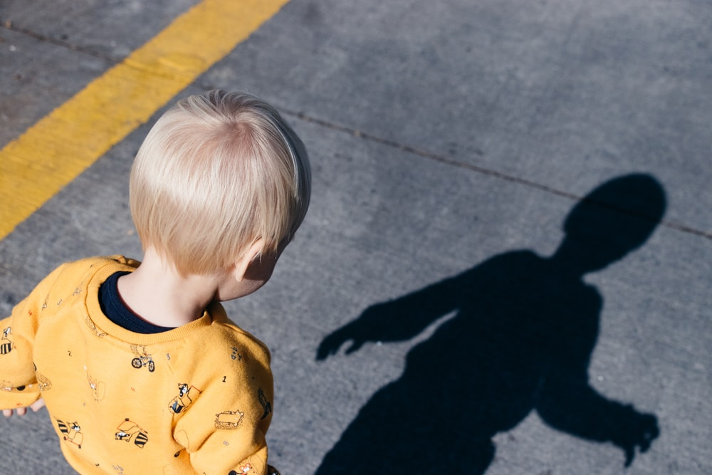 boy standing on roadway looking on his shadow at daytime