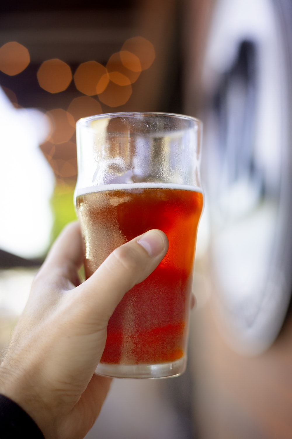 person holding pilsner glass