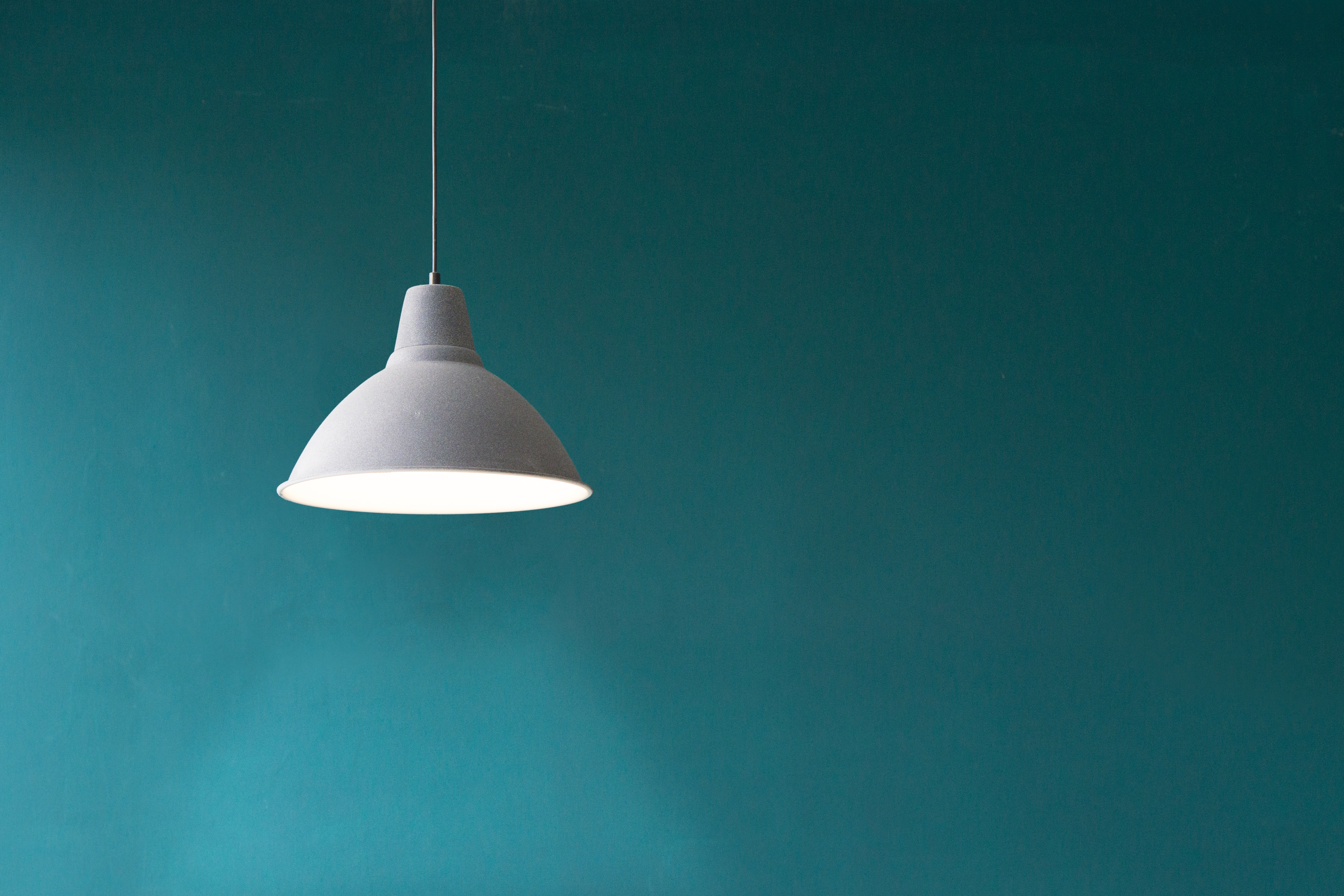 white pendant light in front of green wall