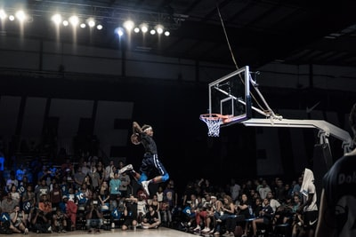 man jumping and about to shoot the ball in basketball hoop in front of crowd basketball zoom background