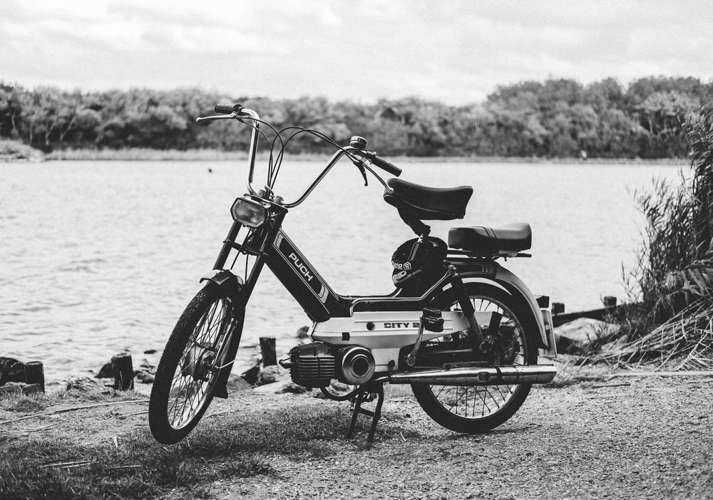 gray moped parked near body of water