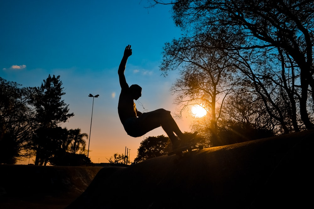 silhouette of man riding on skateboard during sunset