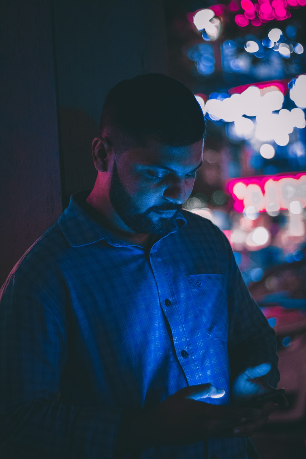 selective focus photography of man holding smartphone with bokeh photography background