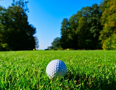 white golf ball on top of green grass field surrounded by green leaf trees golf teams background