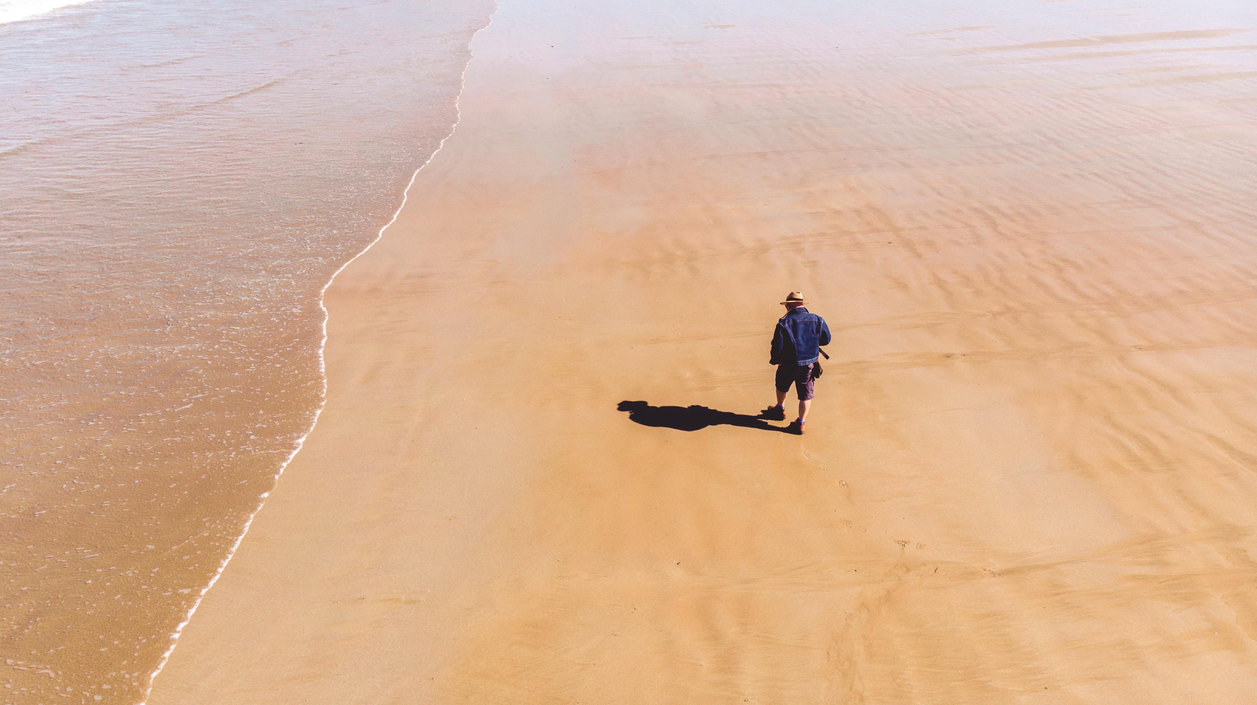 man's shadow reflecting on shore