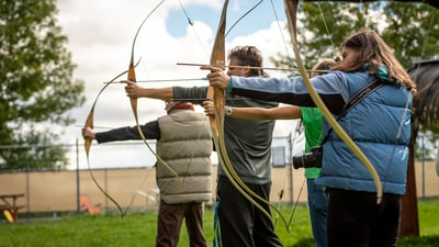 three person practicing using arrow archery zoom background