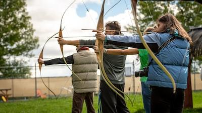 three person practicing using arrow archery teams background