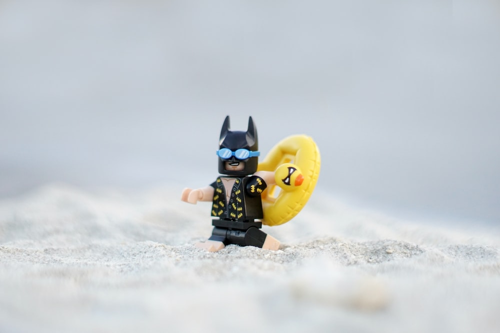 LEGO Batman figurine on white sand at daytime