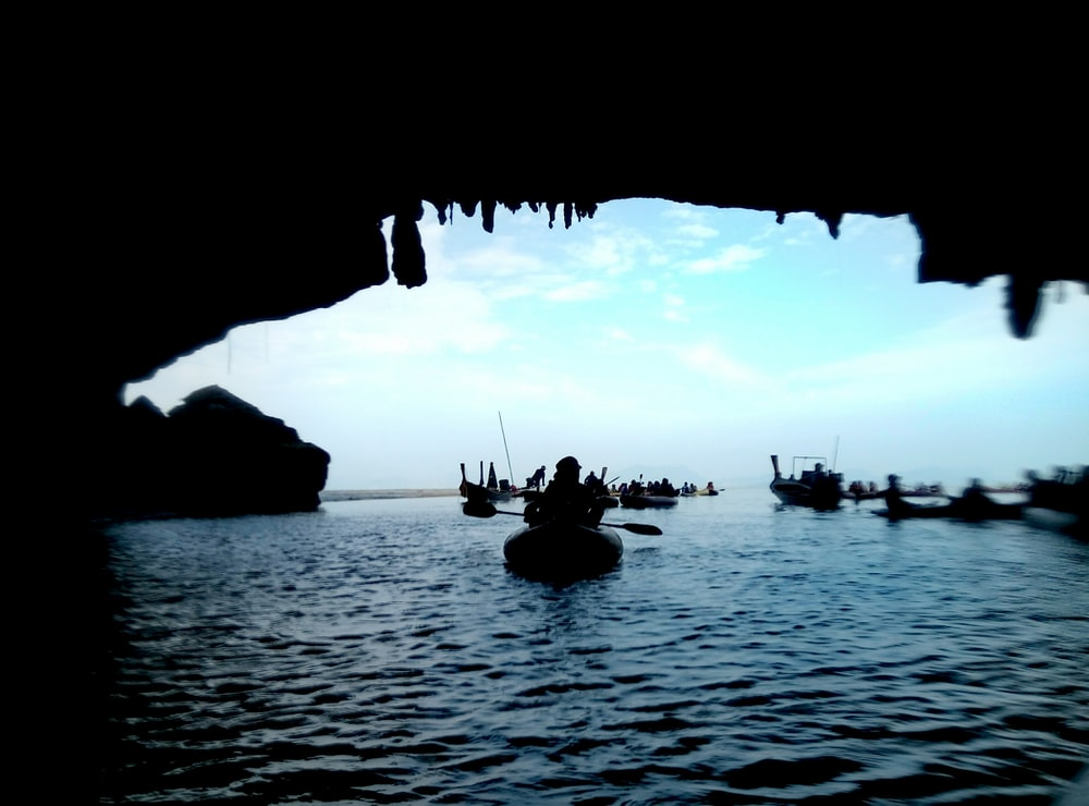 silhouette of boat inside cave
