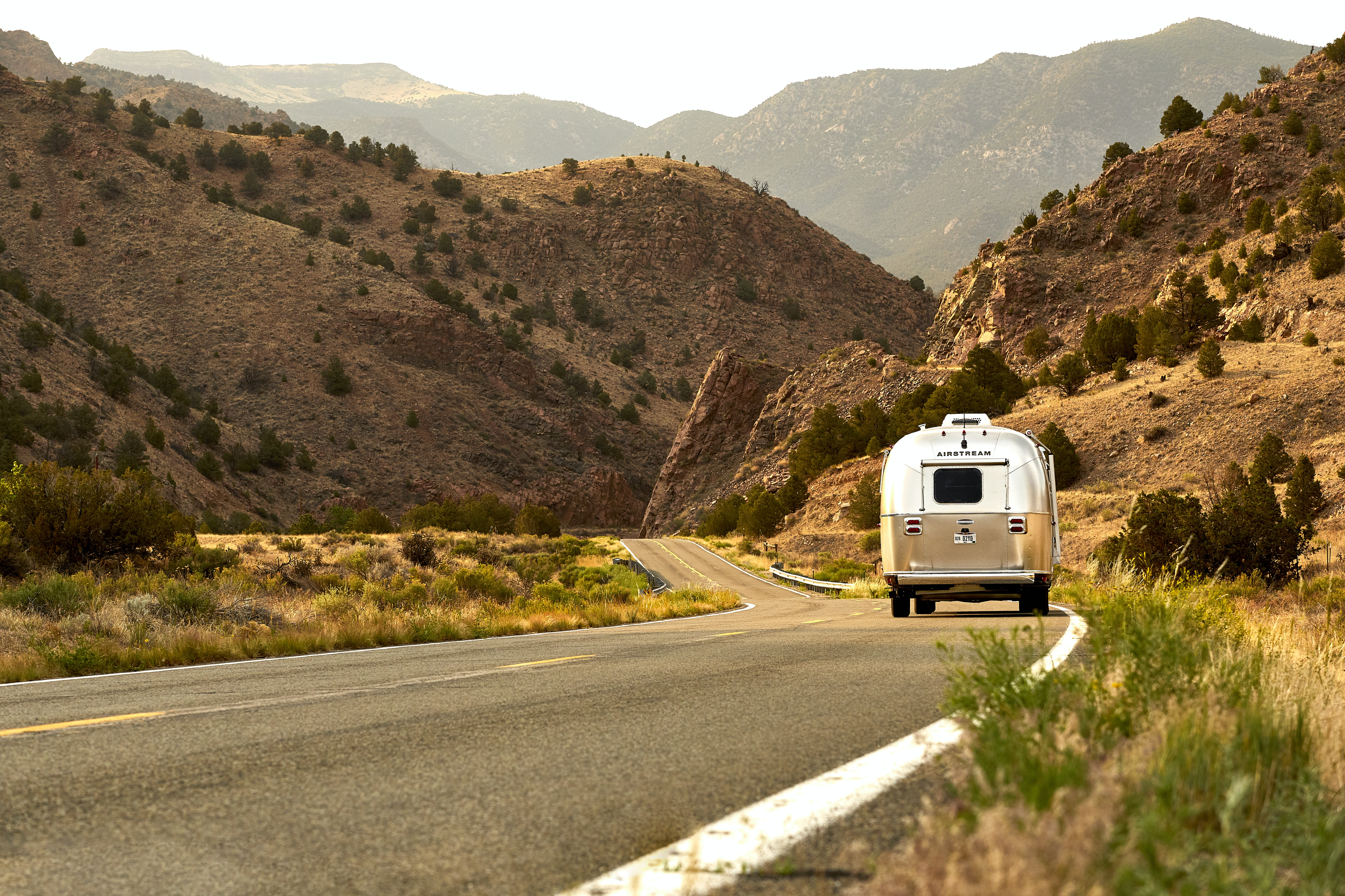 landscape photography of brown and white motorhome on road