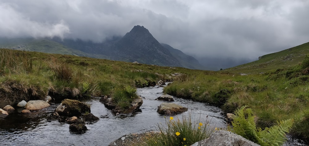 river in the middle of grassy mountain during cloudy day