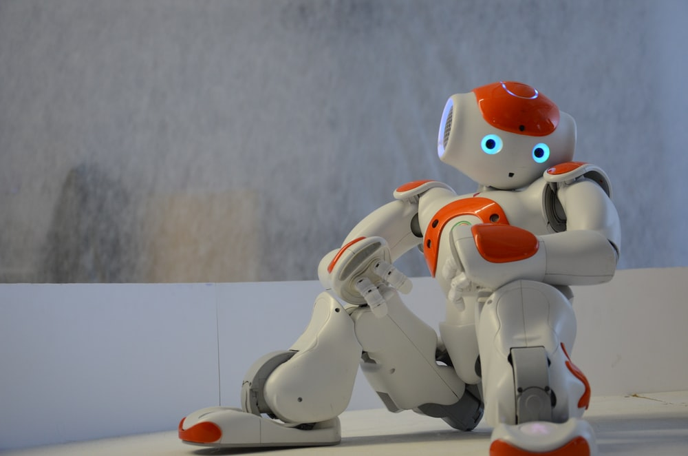 white and orange robot near wall