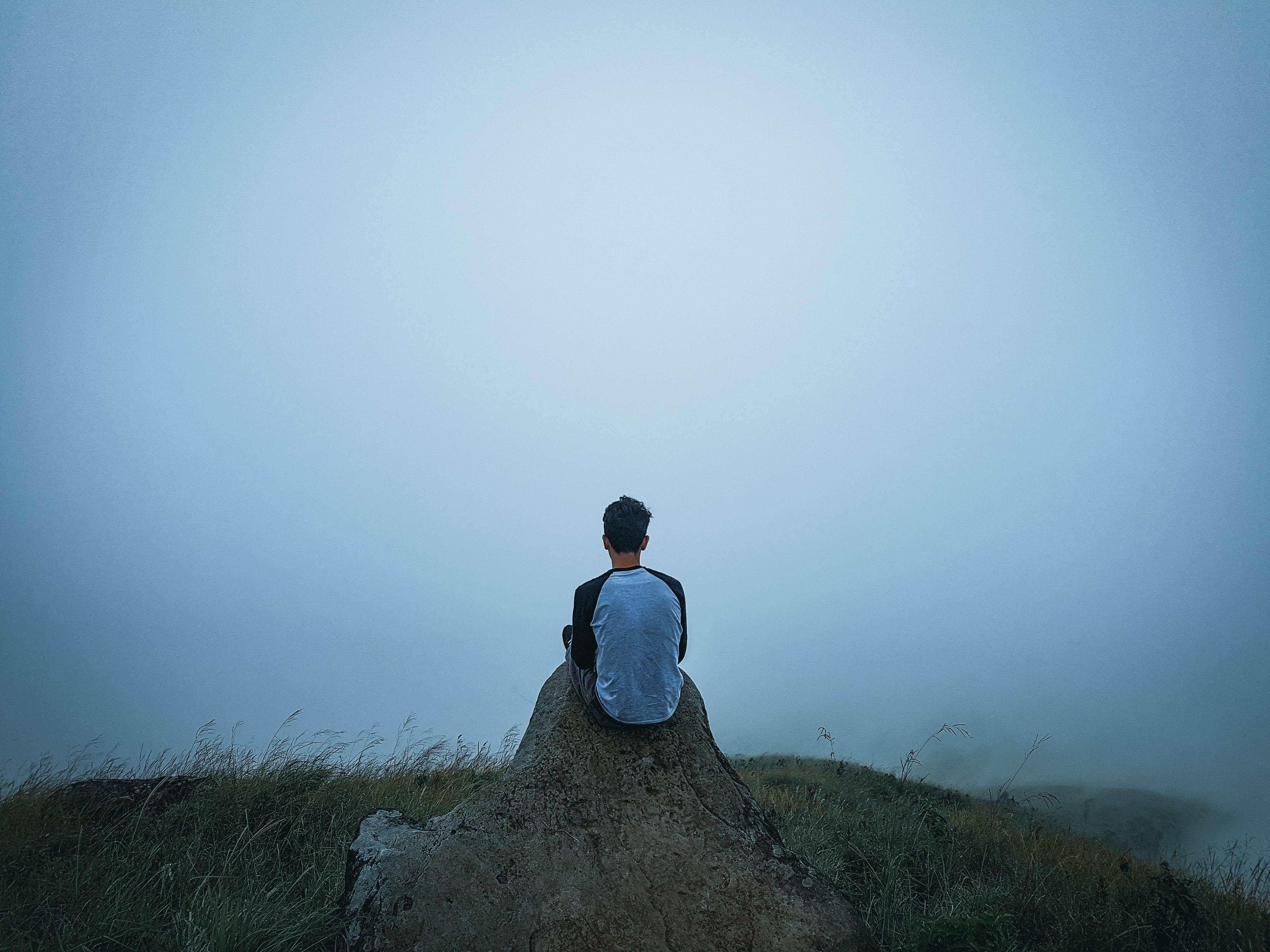 man sitting on a cliff