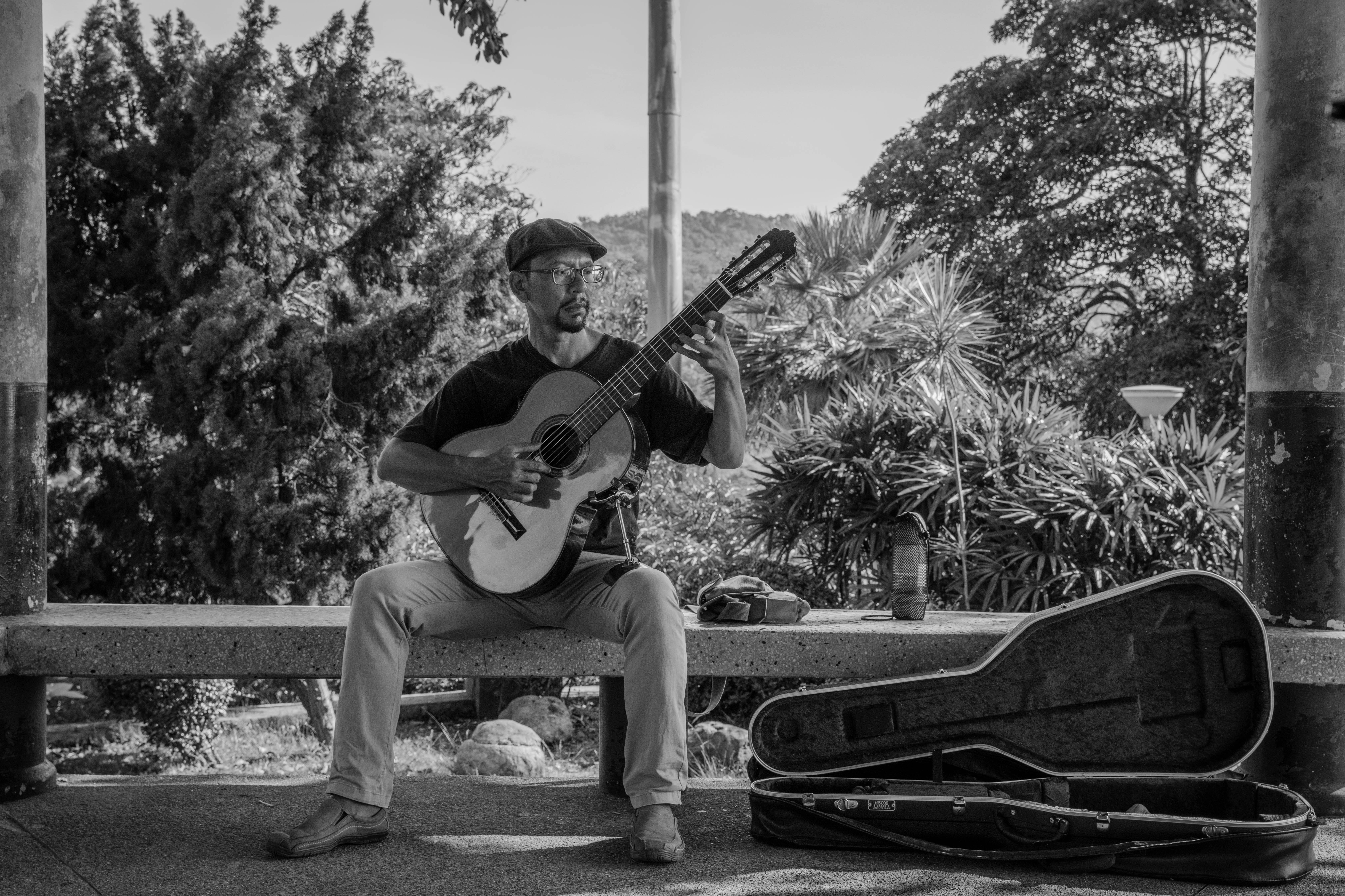 grayscale photography of man playing classic guiar