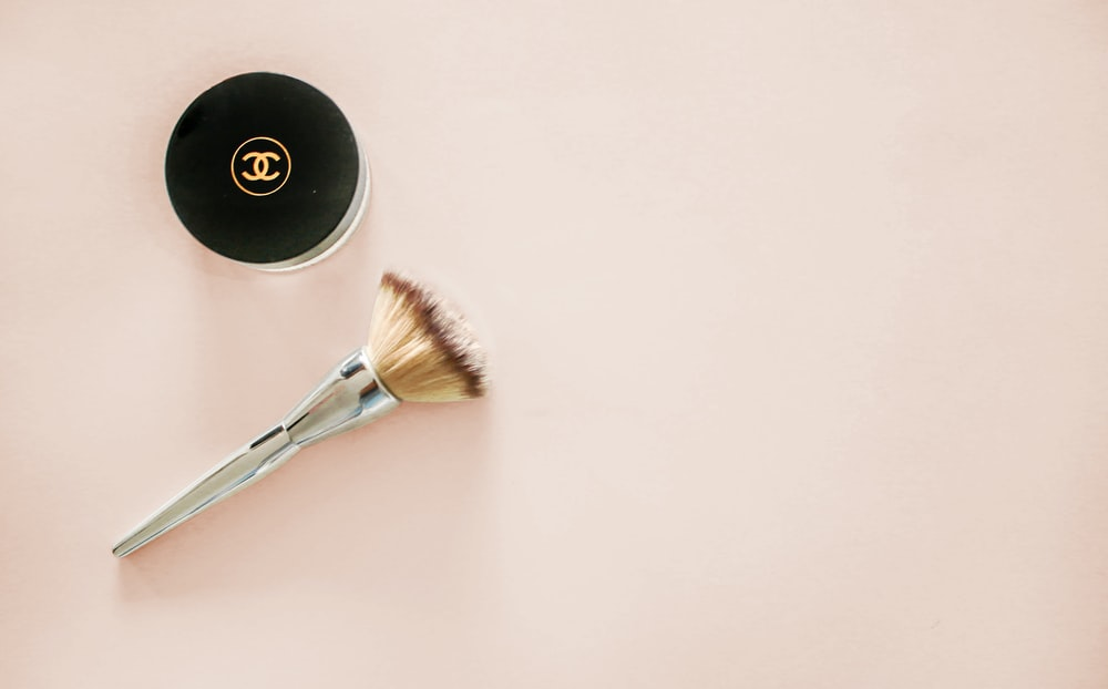makeup brush and Chanel compact jar on beige surface