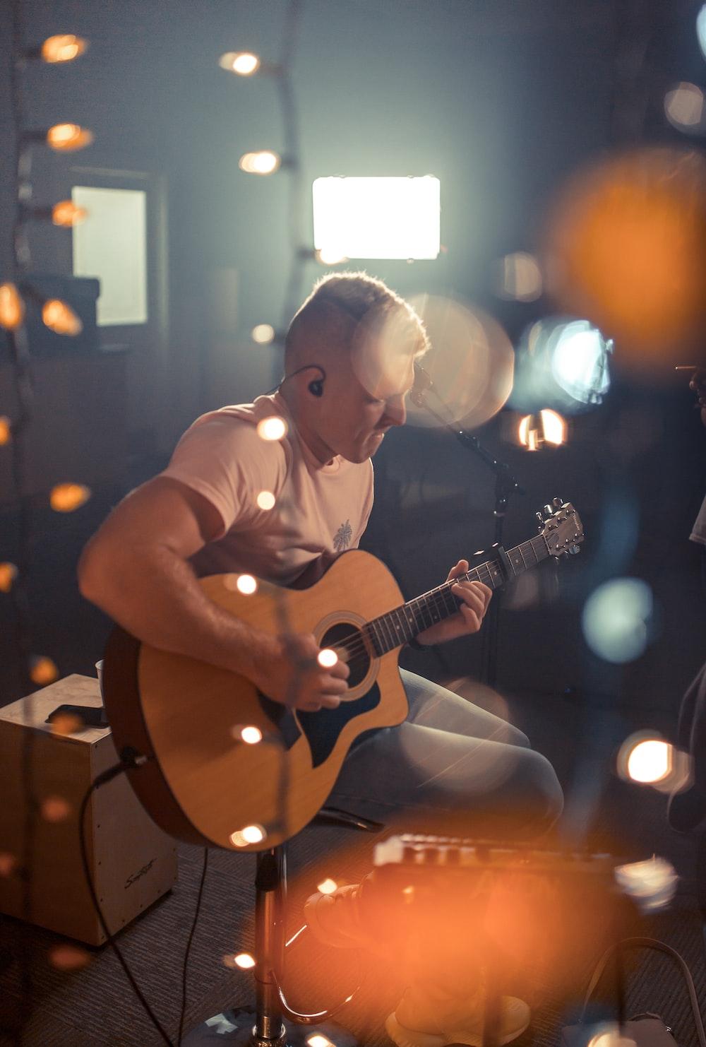 bokeh photography of man playing guitar