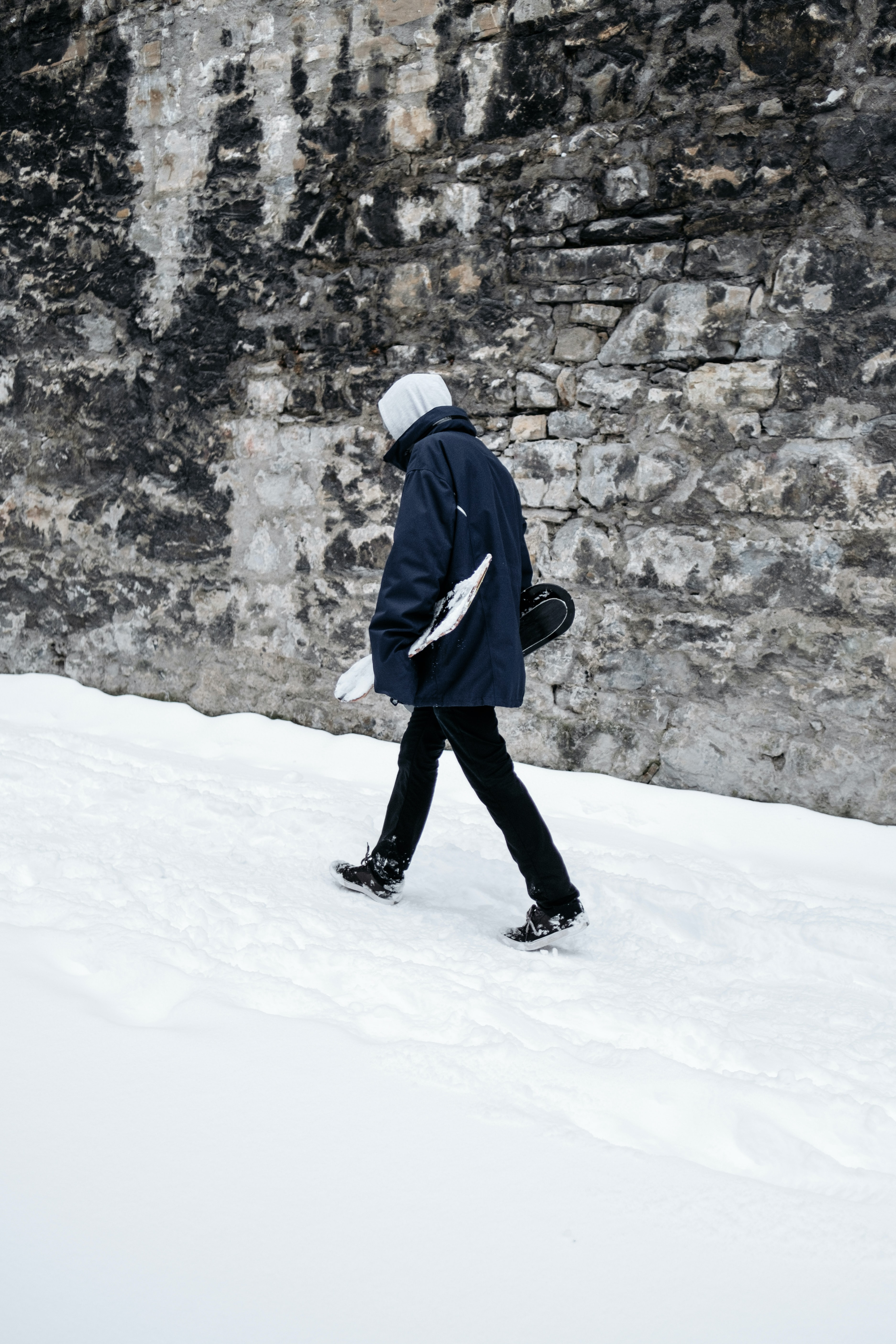 man walking on snow path