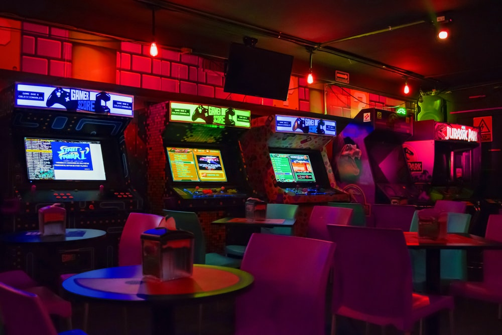 arcade machines near tables and chairs in dim-lit room