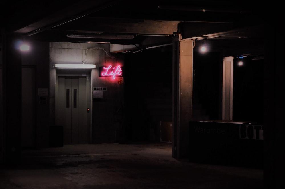 turned-on pink neon sign beside door