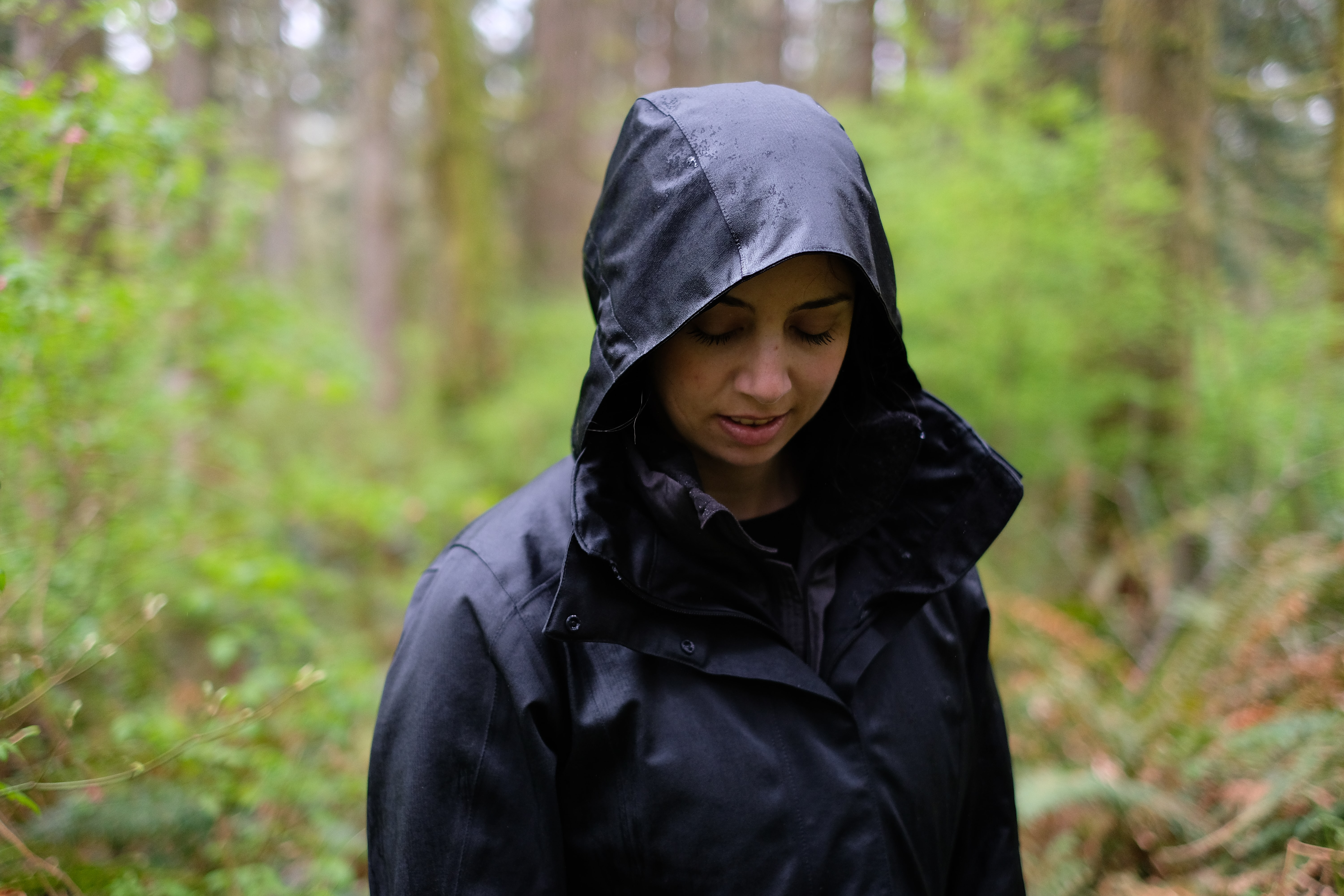 woman standing in forest while looking at the ground