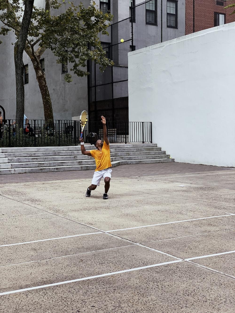 man wearing yellow shirt playing tennis